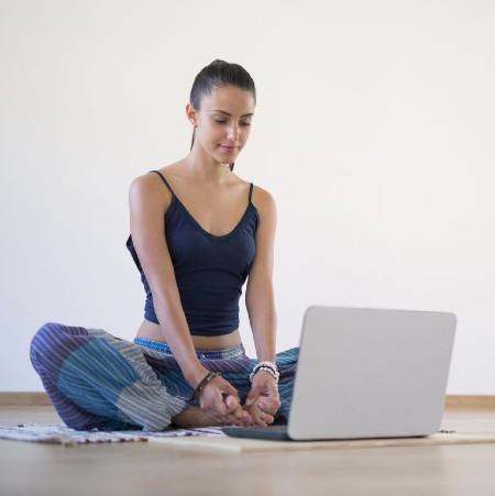 パソコンを見ながらヨガする人