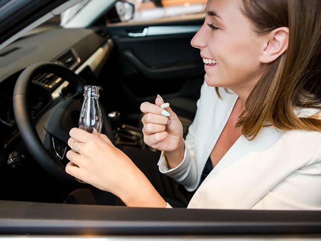 薬を飲んで運転する女性
