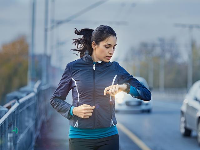 ランニングウォッチを確認する女性ランナー