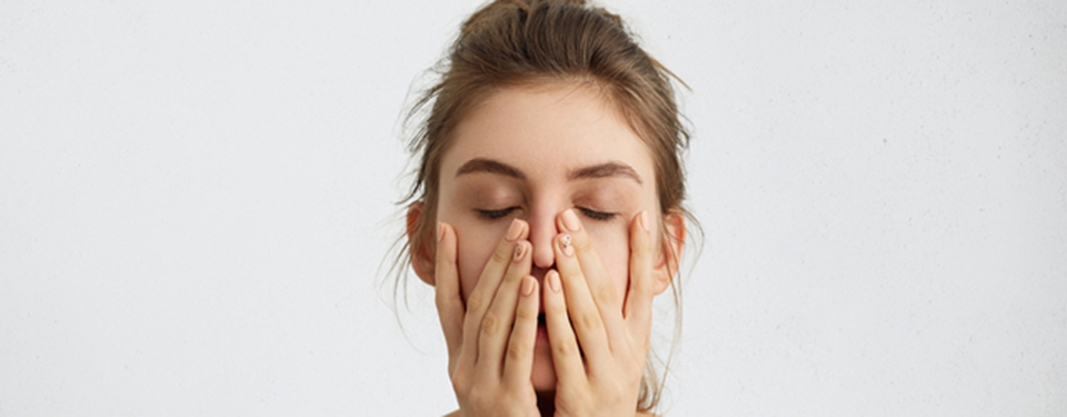 口元を触る女性