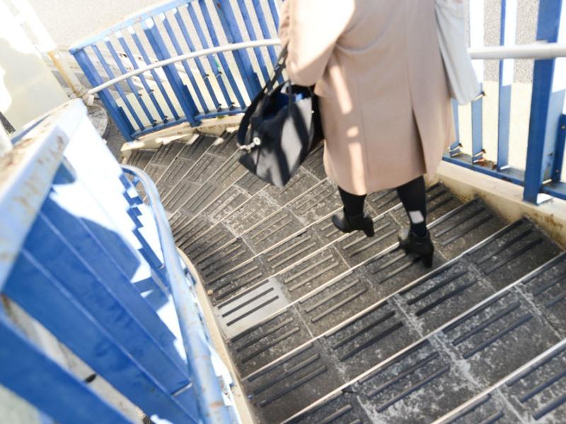 歩道橋を歩く女性