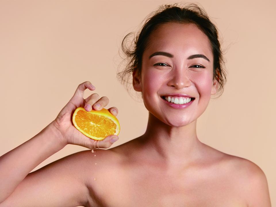 オレンジを持った女性