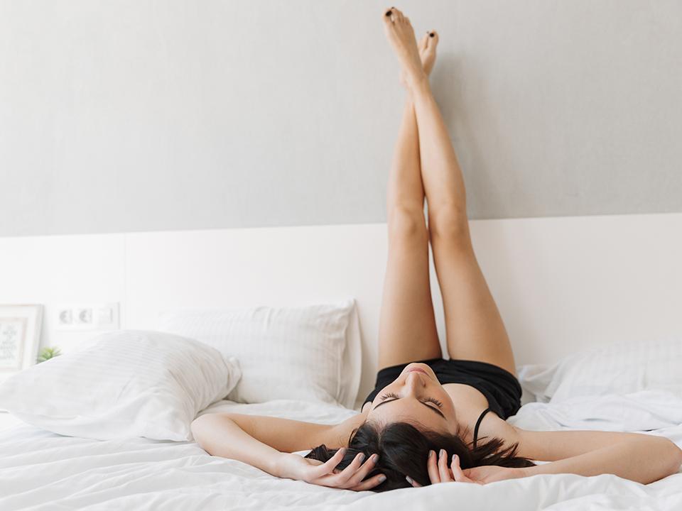 ベッドで脚を上げる女性
