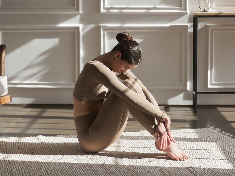 ひざを抱えて座る女性