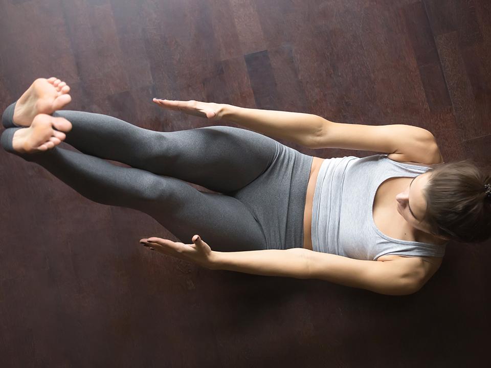 脚を上げて腹筋エクササイズする女性