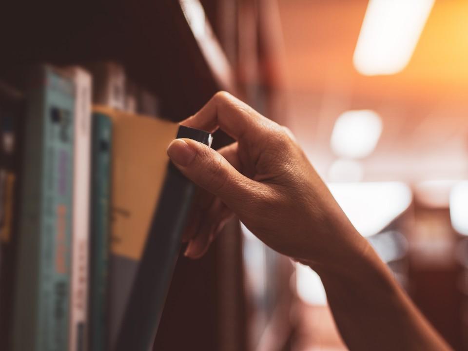 本をとる手