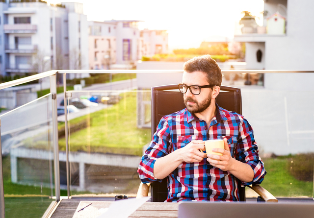 Businessman with cup of coffee sitting on balcony, relaxing