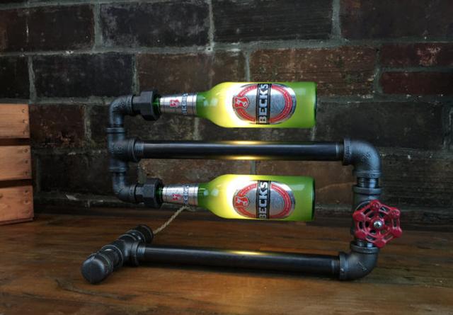 配管に空いたお酒のボトルを取り付けた照明「Beer Bottle Lamp」の紹介です。すべてハンドメイドで、一点ものあります。スチームパンクな風合いがかなりかっこいいです。ハードボイルドなインテリアを演出してくれます。1