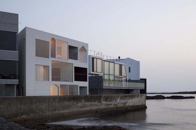 """吉村靖孝建築設計事務所による、海に面する「Nowhere but Sajima」は、この敷地がもつ1番の強みである""""海への眺望""""を活かしきった貸別荘。各部屋から見える海の表情が、まったく異なるように作られています。レンタルは1週間単位で可能です。"""