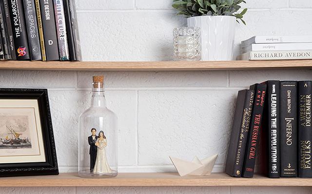ユーモアあふれる雑貨をデザインするPELEG DESIGNがデザインした、底が抜けて好きなものを入れて飾れるペットボトル「Impossible Bottle」を紹介します。部屋に合わず置き場所に困っているもらいものや植物など、このボトルに入れたらなんだか特別感が出ます。新郎新婦のフィギュアが入ってます。