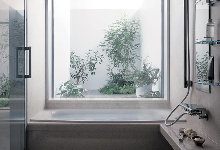 スタイリッシュでウッディなバスルーム。窓の外にはグリーンが