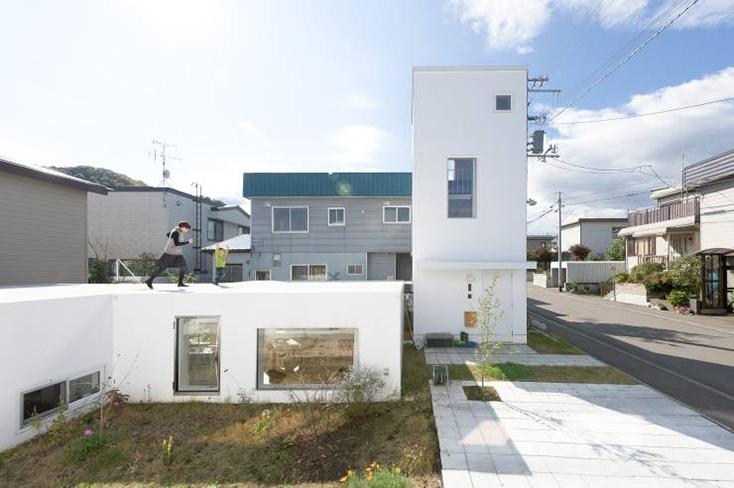 HIROSHI KUNO + ASSOCIATES(久野浩志建築設計事務所)による『KUMAGAI HOUSE』の紹介。高度経済成長期からバブル期にかけて増えたベッドタウンに建つ、低層平屋と高い棟を組み合わせた住宅で、開放的で明るい家ができた。2
