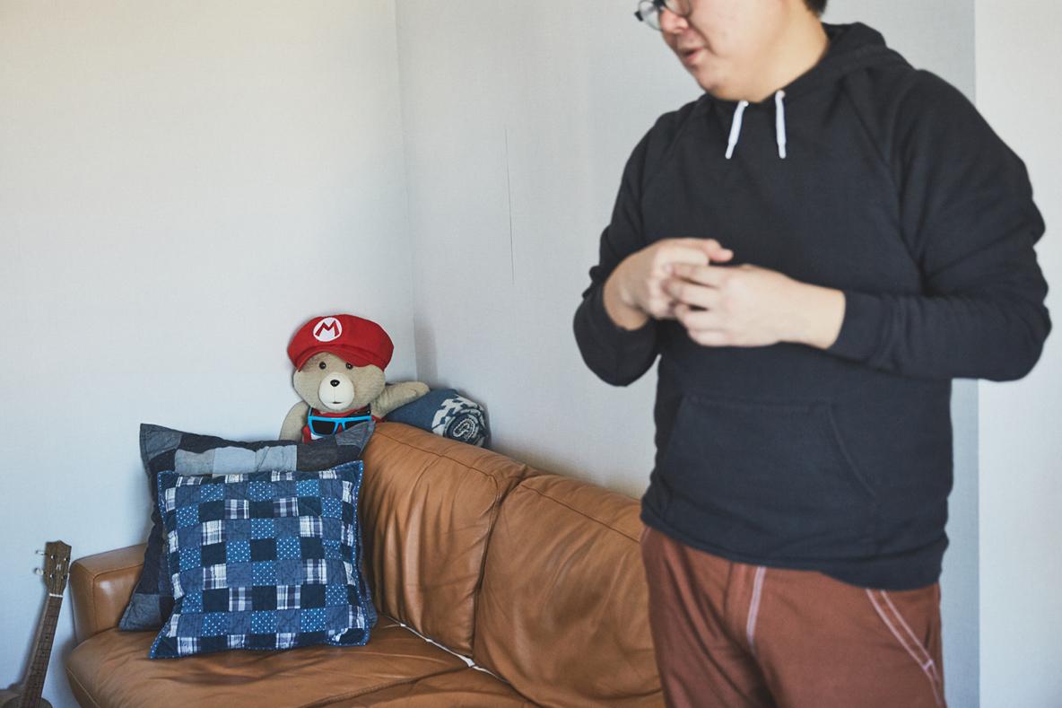 IDEEのソファとA.P.CのクッションカバーとTEDのぬいぐるみ