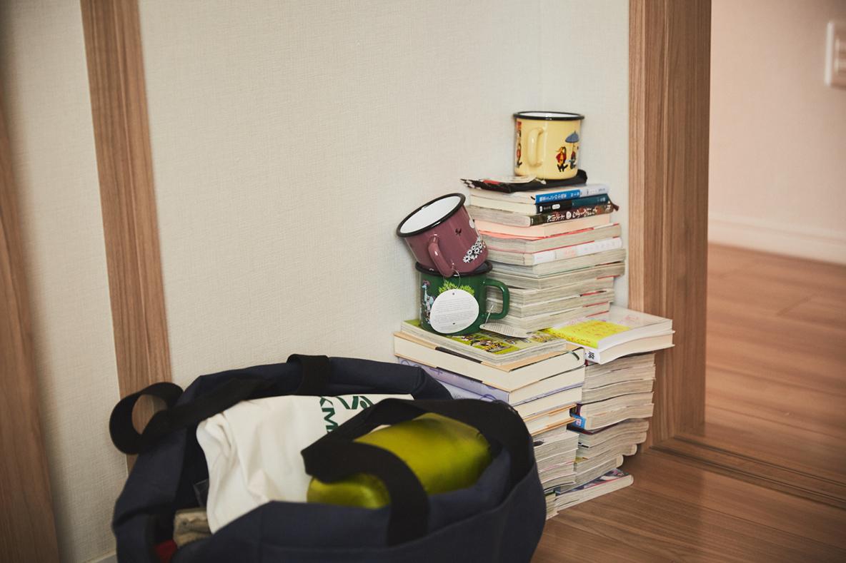 ムーミンのマグカップと、本を床に積ん読する様子