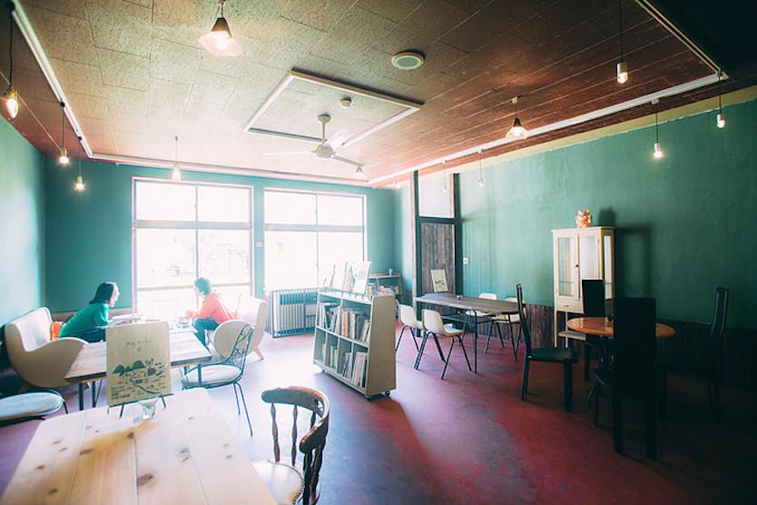 カフェは、新緑の頃の景色と同じ緑の壁で落ち着く空間
