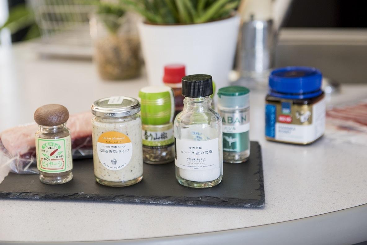 キッチン後ろの棚には、塩やスパイス、沖縄のピイヤーシ、ディップなどの調味料がスタンバイ
