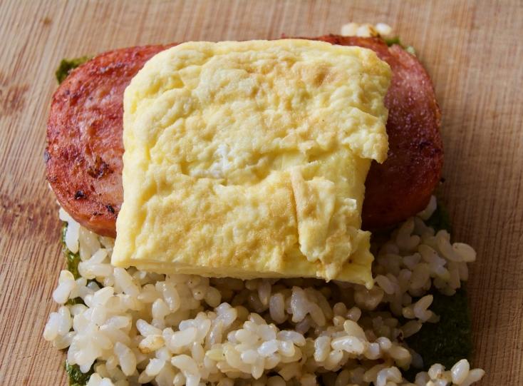 ご飯の上にスパムと焼き卵をのせて、折りたんで少し上からギュッと押したら完成