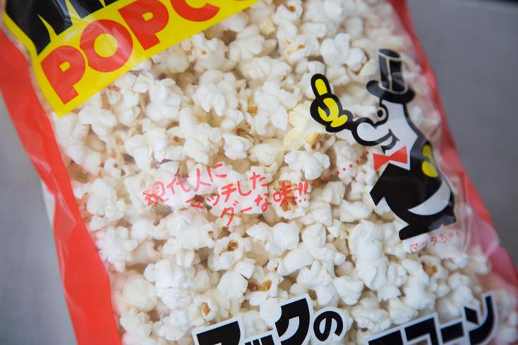 あぜち食品の「マックのポップコーン(しお味)」とは、日本各地の名物を集めた物産館で出合った。袋に描かれた「マックちゃん」なるキャラクターと、「現代人にマッチしたグーな味!!」という謳い文句に惹かれて購入し、帰ってからホームページを見た。