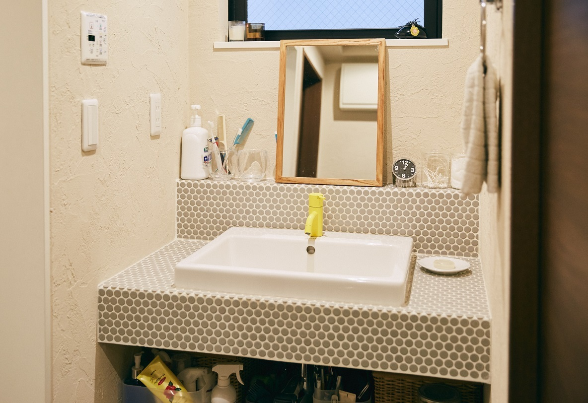 丸いタイル張りに白目地が効いた洗面所