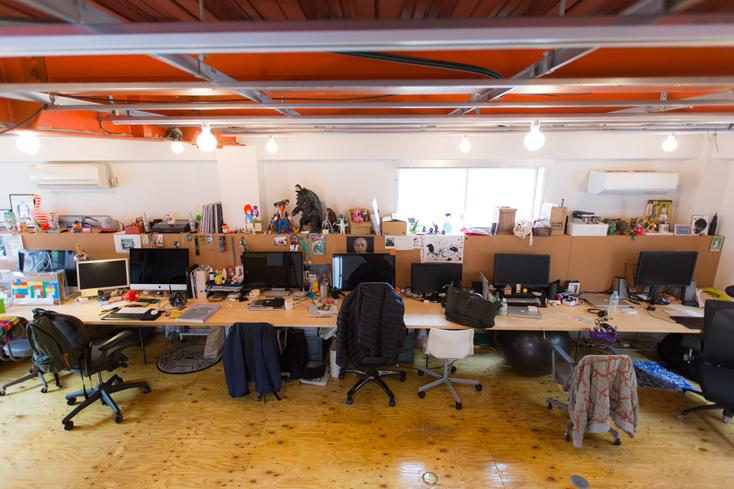 印象的なのは、2Fの作業フロアの端から端まで9mにわたって長くのびるデスク。「オフィスのなかで特に気に入っているのは、部屋に合わせてオリジナルでつくってもらった机ですね。9mどかーんとあって、人が大勢いるときにもつめれば座れるし、作業する人数の増減がフレキシブルです」
