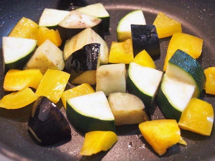 フライパンに米油またはサラダ油、ズッキーニ、茄子、パプリカを入れてざっと混ぜて、油を馴染ませてから火をつけ、中火でこんがり焼く