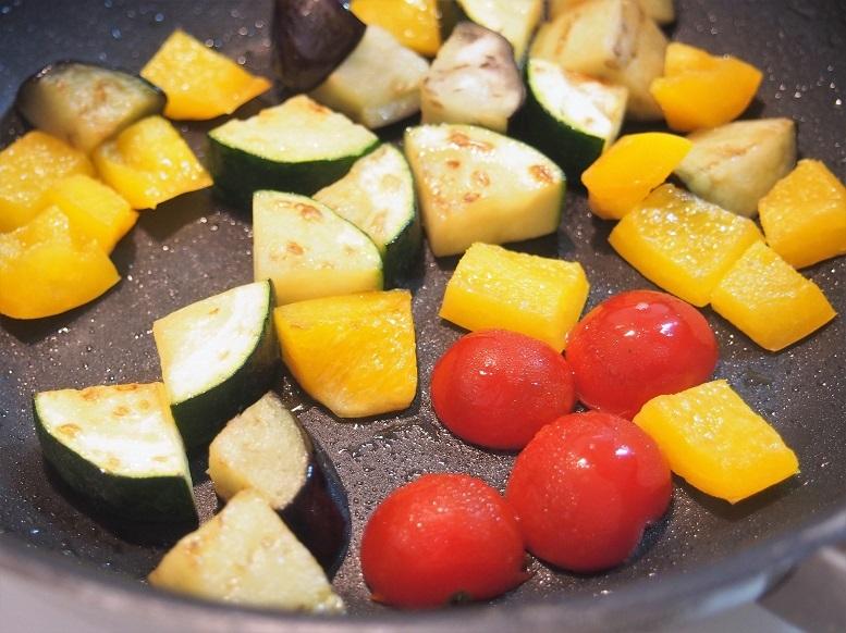 片面が焼けたら裏返し、そのタイミングでミニトマトの断面を下にして入れ、同様に焼く。野菜は焼けた順に取り出そう