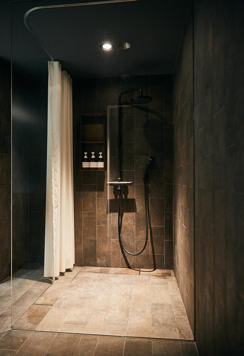 三栄水栓製作所とサポーズデザインオフィスのホテルのバスルームのようなスタッフ用シャワールーム