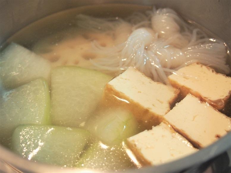 お鍋に出汁、酒、塩を加えて混ぜ、冬瓜、れんこん、厚揚げ、糸こんにゃくを加えて火にかけ、沸騰したら弱火にし、落し蓋をして20分煮る