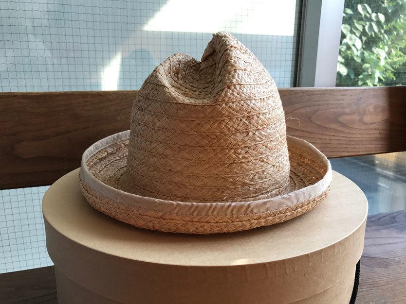 """「……. RESEARCH」のストローハット BY プロデューサー・尾田。頭部が山脈のように変形した""""……. RESEARCH [MOUNTAIN RESEARCH]""""のストローハット。ヴィヴィアン・ウェストウッドの通称「マウンテン・ハット」を想起させられるけれど、より小ぶりで、シンプルな形となっている。麦わら帽子とか、普段かぶると妙にリゾート感が出て思わずアロハシャツを着なくてはいけないような罪悪感を持ちがちなところ、こちらはシンプルな白Tや、レゲエっぽくポロシャツに合わせるなど、あわせのバリエーションが意外と豊富なので夏は重宝しそう。"""