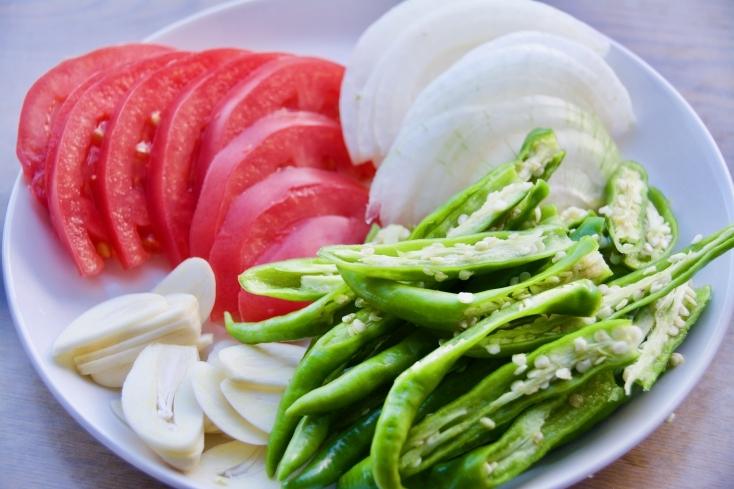青唐辛子、ニンニク、タマネギ、トマトを食べやすい大きさに切る