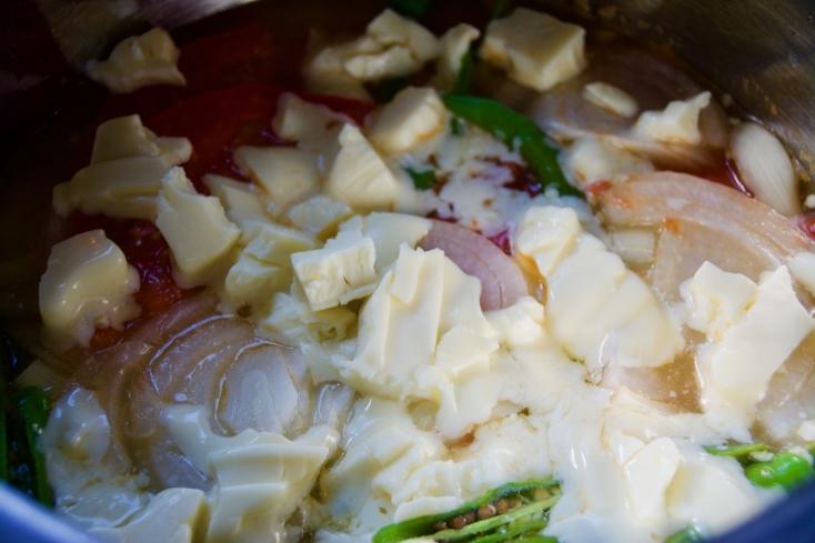 全体的に材料がしんなりしてきたら、チーズを入れてさらに煮込む。チーズが溶けはじめたら全体を大きくかき混ぜ、お好みでパクチーを盛りつければ完成