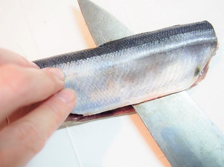 腹側を手前にして置き、中骨に当たるように包丁を入れる。裏返し先ほど捌いた側を下にして、背側が手前に来るように魚を置く