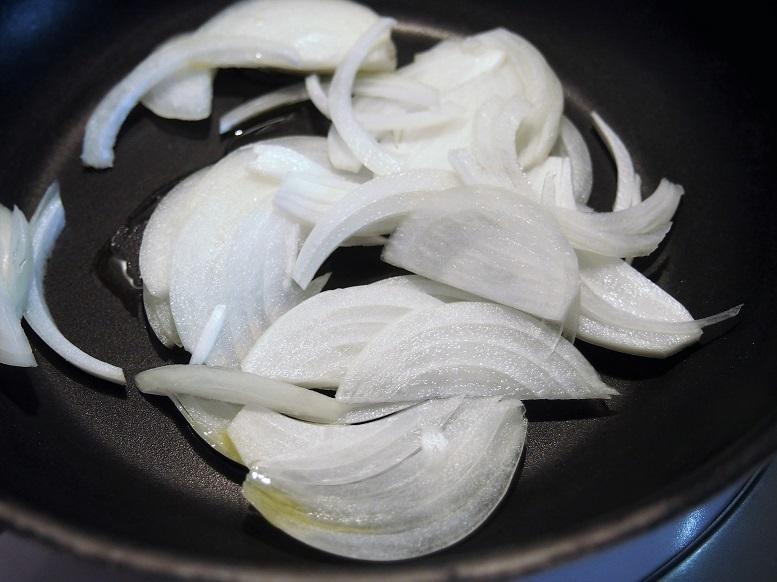 たまねぎを薄切りにし、フライパンにオリーブオイルと共に入れ、しんなりするまで炒める