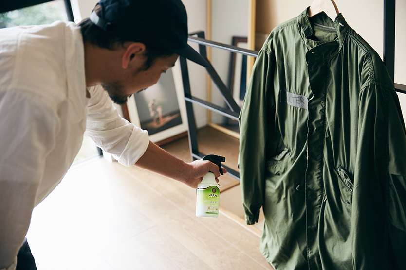 服の臭いに消臭剤を使う男性