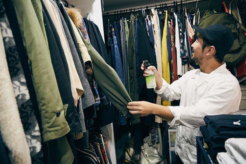 服に消臭剤をかける男性