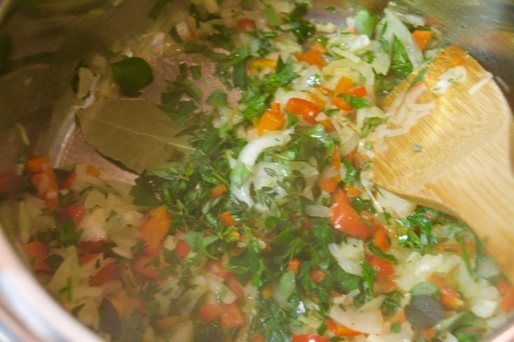 鍋に刻んだオレガノ、タイム、唐辛子、月桂樹の葉を加えてさらに炒める