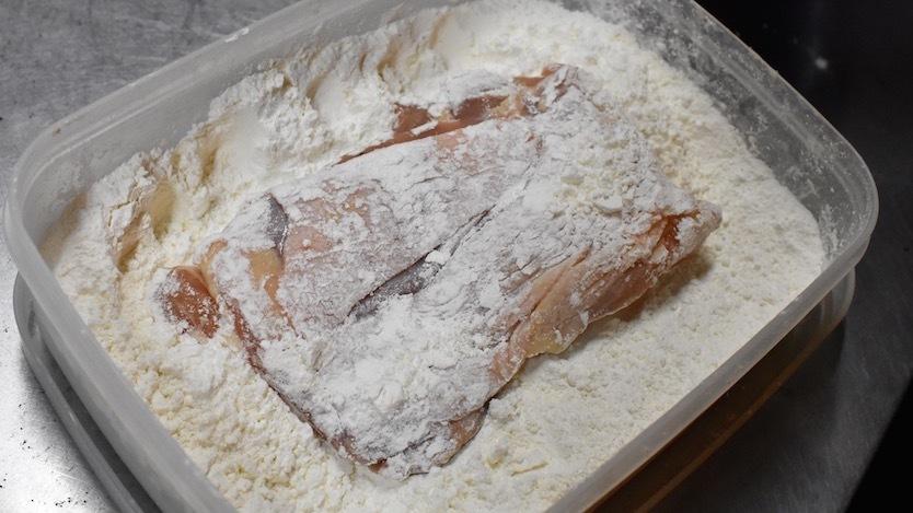 両面にまんべんなく小麦粉をつける。ポイントは、小麦粉をしっかりはたいて落とすこと。小麦粉にムラがあると、卵がつきにくくなるため