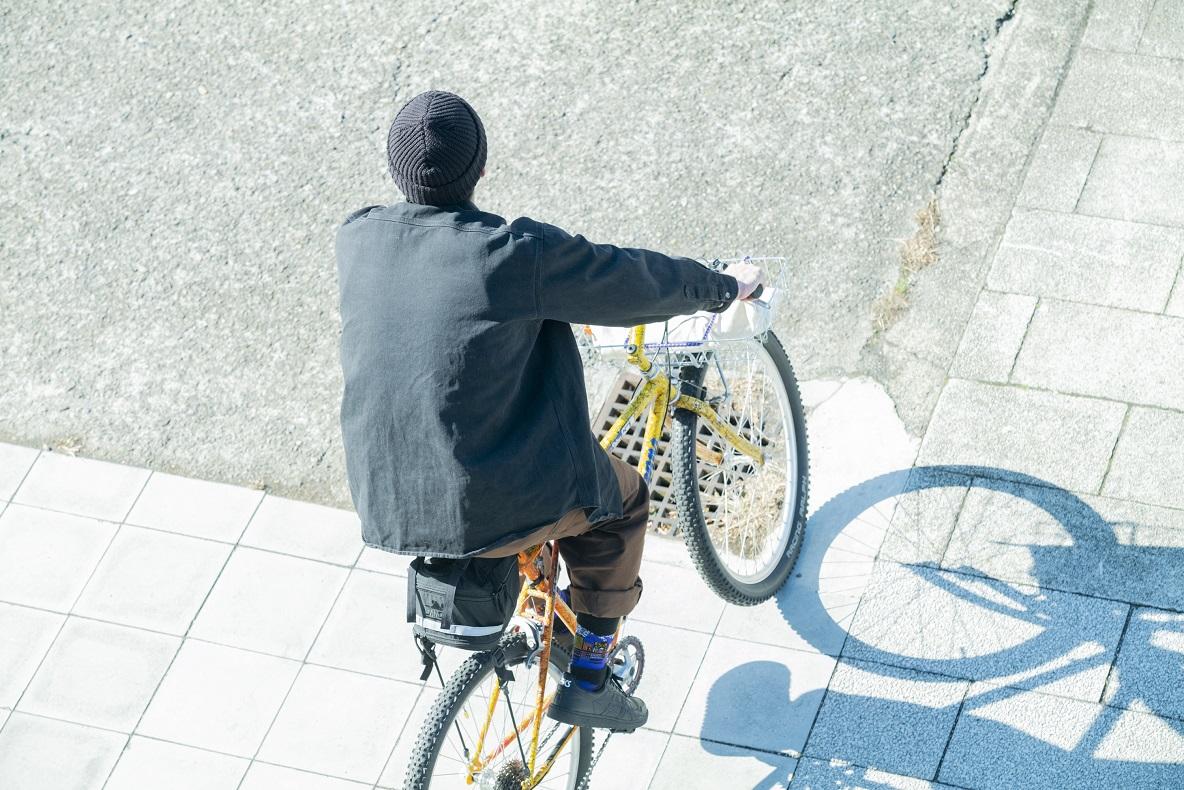 自転車に乗る木村さんの後ろ姿