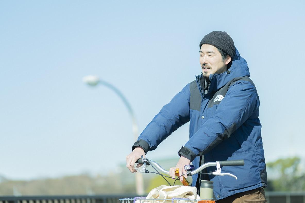 自転車のハンドルに手をかけながら話す木村さん