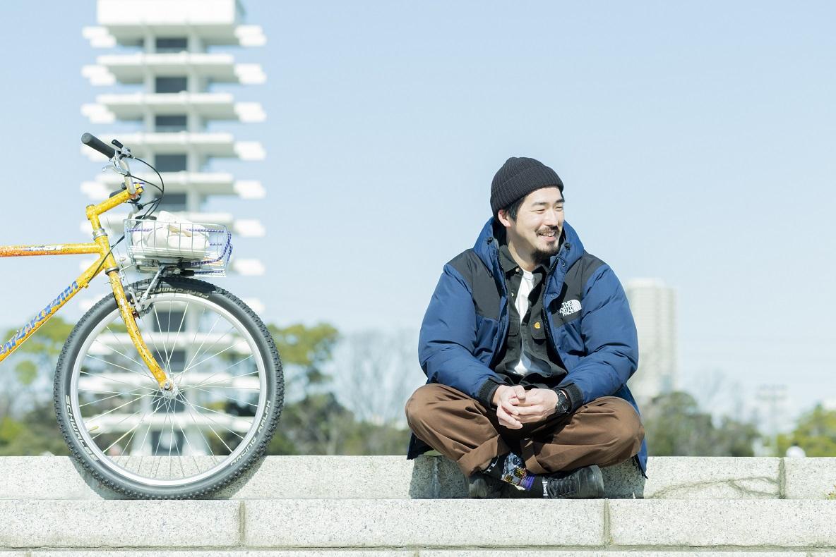 自転車を横に立てかけ、階段に腰かける木村さん