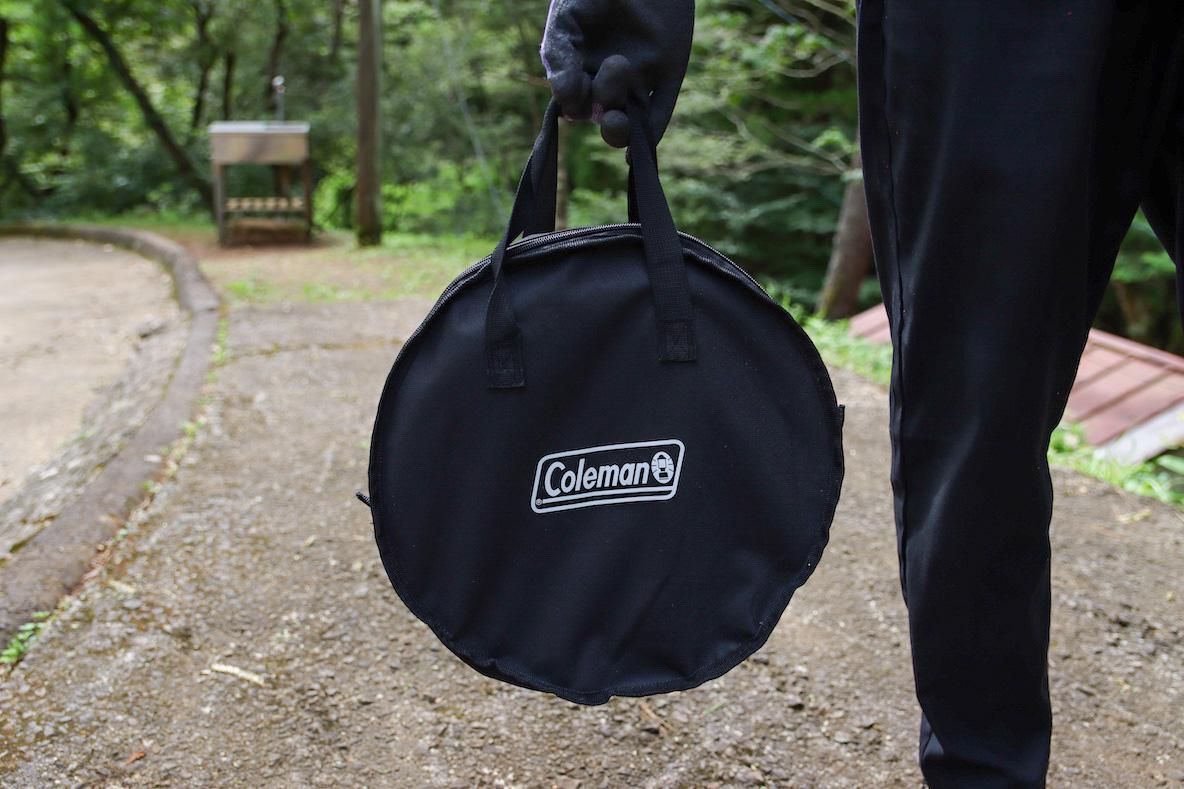 コールマン 「ファイアーディスクソロ」の収納袋を持つ男性
