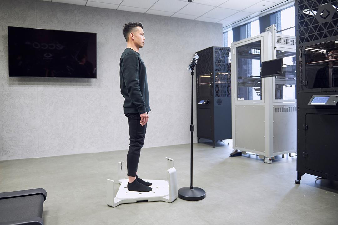 3D足型計測器に乗る菅原さん。わずか15秒で足を隅々までスキャンし、あらゆるデータを計測する。