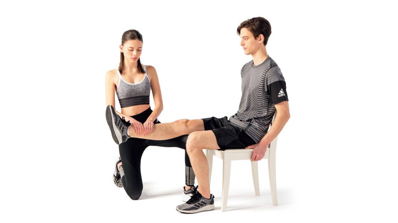 椅子に深く腰掛け、片脚をまっすぐ伸ばす。パートナーは両手で伸ばした脚の脛を持ち、上からプレッシャーをかける。