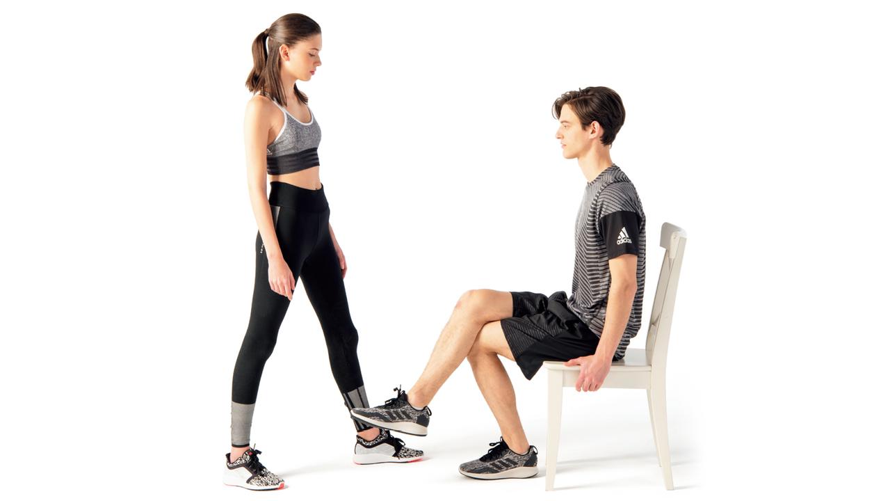 椅子に深く腰掛けて両脚を組む。