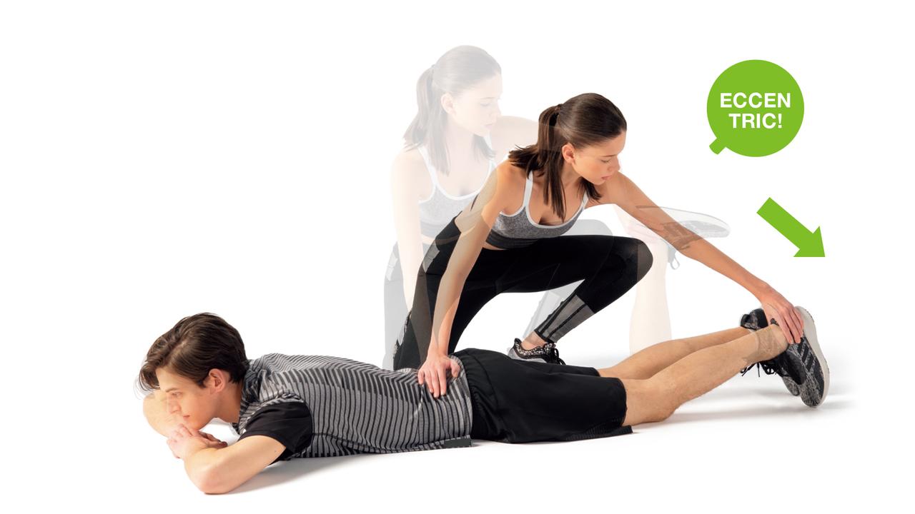 パートナーは片手を相手の腰に置き、反対側の手で相手の踵を摑んで床に引き下ろすように圧をかける。圧に抵抗するようにエキセン。