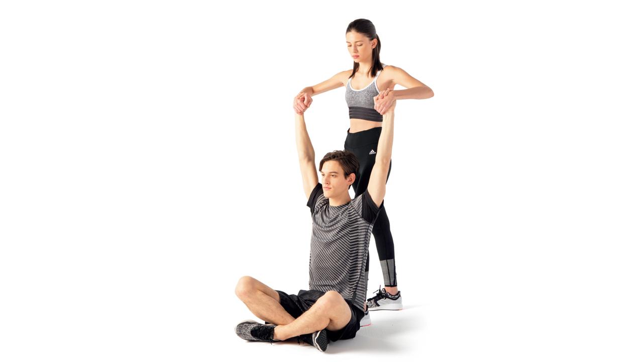 あぐら姿勢で床に座り、両手を真上に伸ばす。