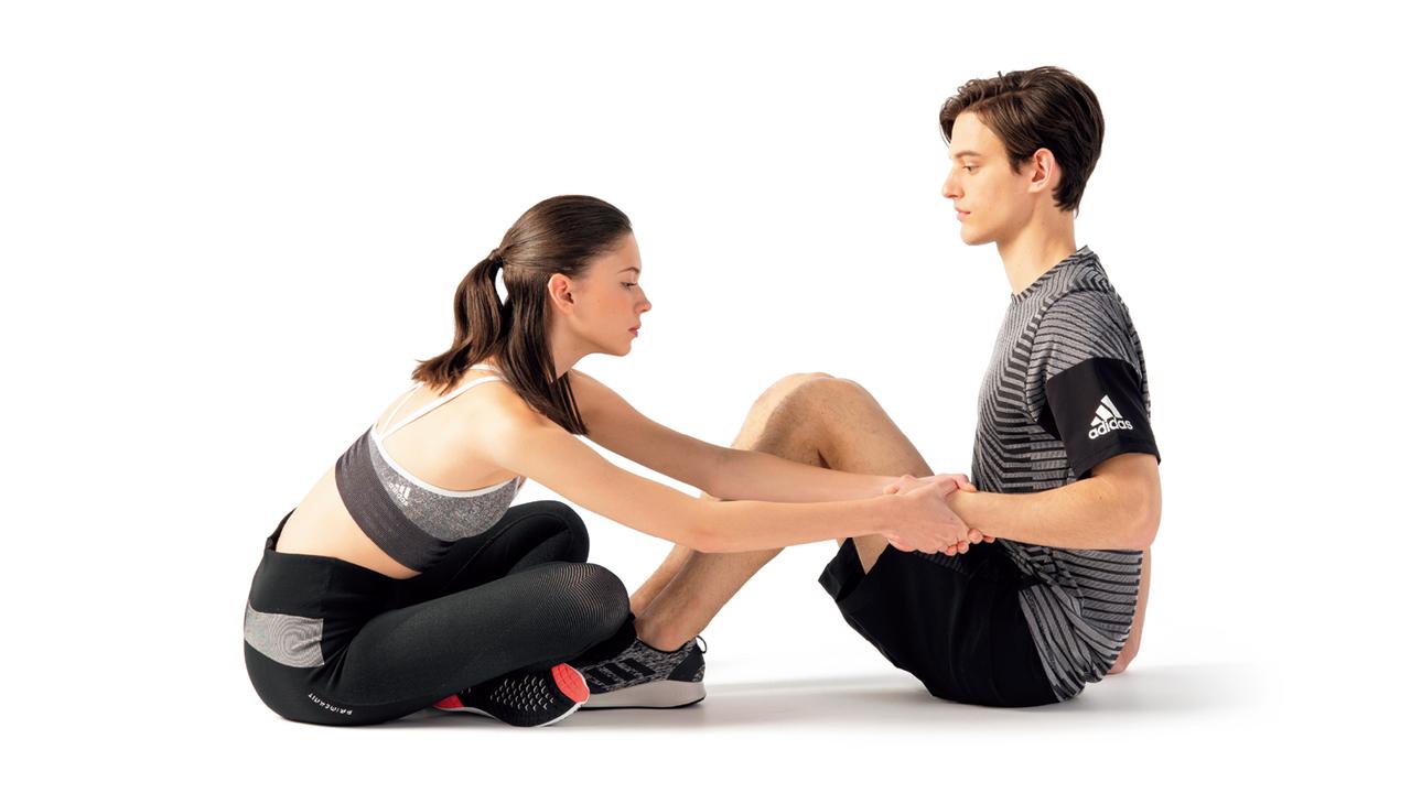 パートナーと向き合うようにして床に座り、両膝を立てる。片方の肘を直角に曲げて脇を締める。