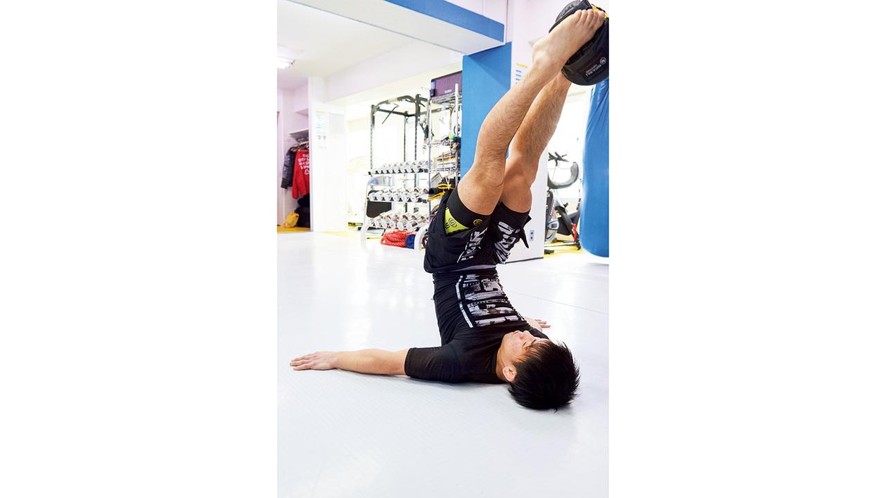 仰向けに寝て反動を使わず両脚を上げ、膝を伸ばす。足先は顔の真上に。