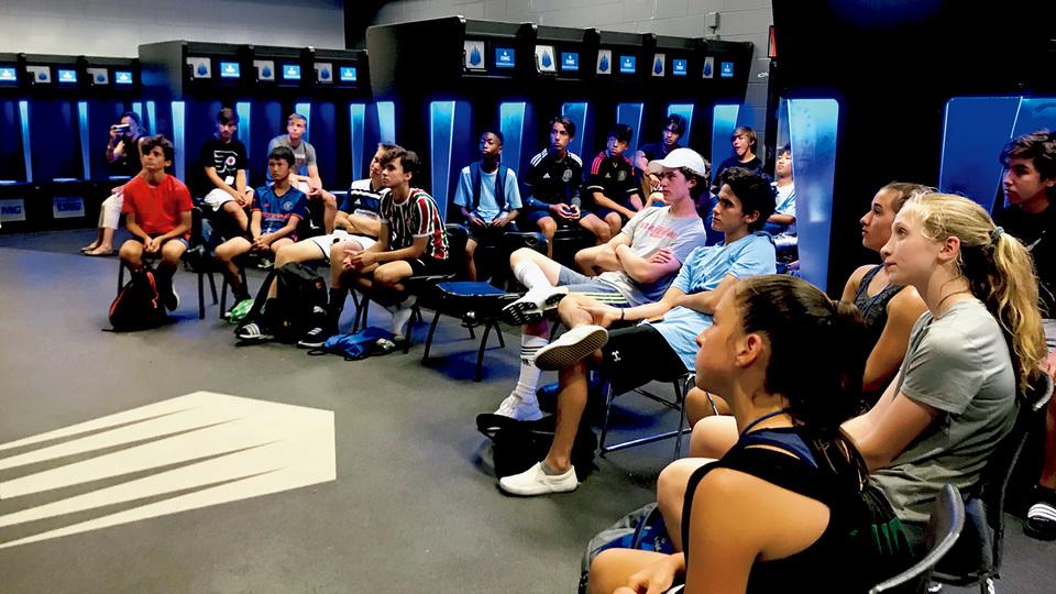 ブルーにライトアップされたロッカールーム。プロさながら、集中してサッカーの講義を聴くIMGアカデミーの子供たち。