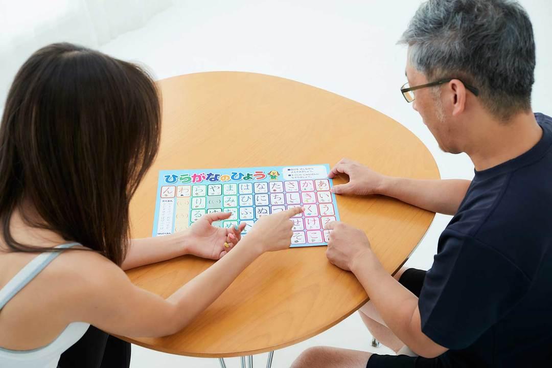 子ども向けのひらがな表を見ながら「この文字は?」「こっちはどう?」と話し合う2人。宮河さん、だんだんマジモードになってきました!